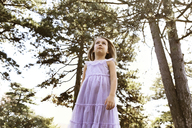 Low angle view of girl looking away while standing in backyard - CAVF05015