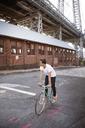 Man cycling on road against Williamsburg Bridge - CAVF05141