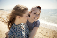 Portrait of happy woman embracing friend while standing at beach - CAVF05150