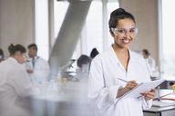 Portrait smiling female college student taking notes in science laboratory classroom - CAIF10010