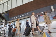 Business people walking pulling suitcases in airport concourse - CAIF10019