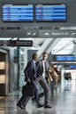 Businessmen running rushing in airport concourse - CAIF10022