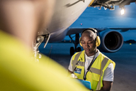 Air traffic control ground crew working under airplane on airport tarmac - CAIF10031
