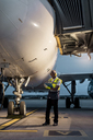 Airport ground crew worker with clipboard under airplane on tarmac - CAIF10034