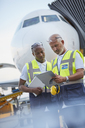 Air traffic controllers with clipboard below airplane on airport tarmac - CAIF10040