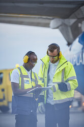 Air traffic controllers with clipboard talking on airport tarmac - CAIF10043