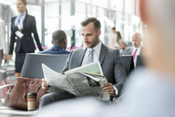 Businessman reading newspaper in airport departure area - CAIF10046