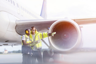 Air traffic control ground crew workers talking near airplane on airport tarmac - CAIF10049