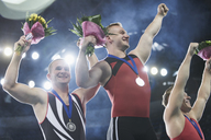 Enthusiastic gymnasts cheering celebrating victory on winners podium - CAIF10097