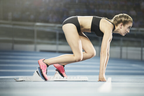 Focused female runner ready at starting block on sports track - CAIF10106