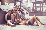 Friends hanging out using digital tablet on sunny sidewalk - CAIF10130