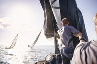 Man sailing on sunny ocean - CAIF10151