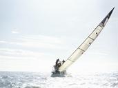 Sailboat tilting on sunny ocean - CAIF10160