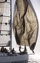 Man adjusting sail on sailboat - CAIF10163