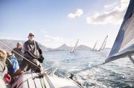 Man adjusting sailboat rigging on sunny ocean - CAIF10166