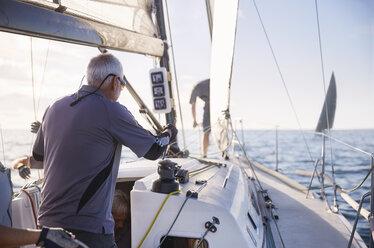 Man adjusting sailing equipment on sailboat - CAIF10175