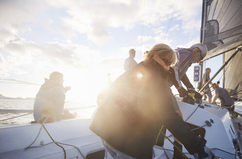 Friends adjusting sailing equipment on sunny sailboat - CAIF10178