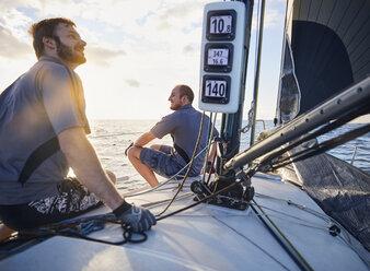 Men monitoring wind on sailboat - CAIF10181