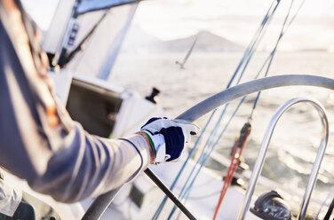 Man sailing steering sailboat at helm - CAIF10184