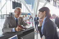 Customer service representative helping businessman with passport at airport check-in counter - CAIF10193