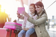 Mother and daughter taking selfie with digital tablet camera at airport - CAIF10202