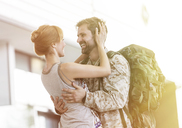 Wife greeting and hugging soldier husband at airport - CAIF10205