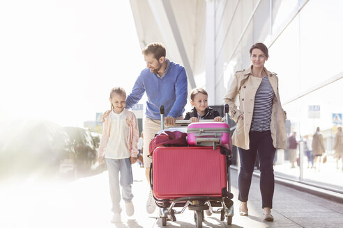 Family with luggage cart walking outside airport - CAIF10208