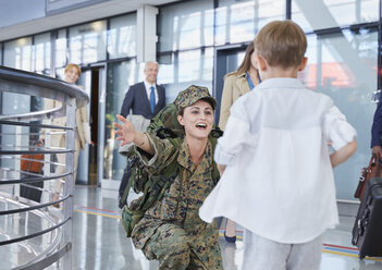 Son running greeting soldier mother at airport - CAIF10211