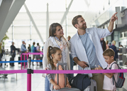 Family with suitcases pointing in airport concourse - CAIF10214