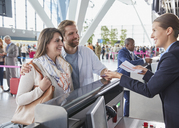 Customer service representative helping couple at airport check-in counter - CAIF10217