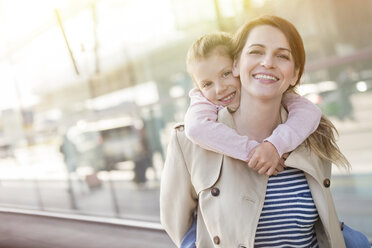 Portrait smiling mother piggybacking daughter outside airport - CAIF10220
