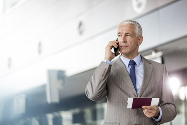 Businessman with passport and airplane ticket talking on cell phone in airport - CAIF10223