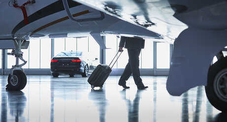 Businessman pulling suitcase outside corporate jet - CAIF10238