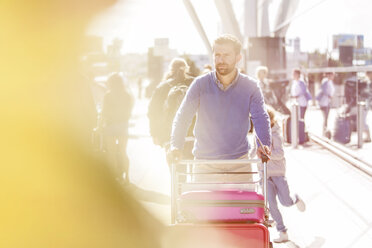 Man pushing luggage cart outside airport - CAIF10241