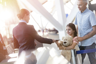Flight attendant checking ticket of girl with teddy bear in airport - CAIF10244