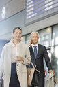 Business people walking and talking on cell phone in airport concourse - CAIF10247