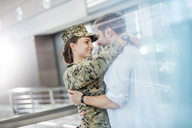 Husband greeting hugging soldier wife at airport - CAIF10250