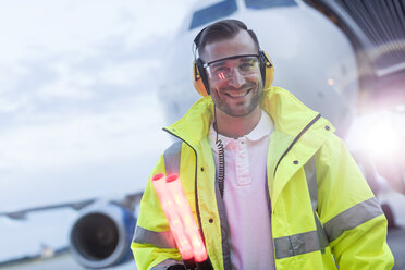 Portrait smiling air traffic controller in front of airplane on tarmac - CAIF10253
