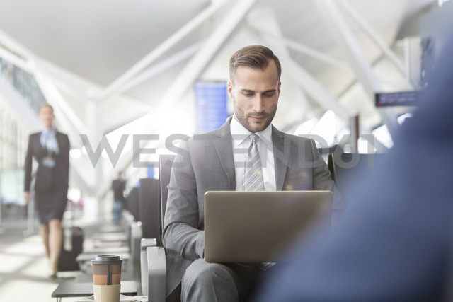 Businessman working using laptop in airport departure area - CAIF10256