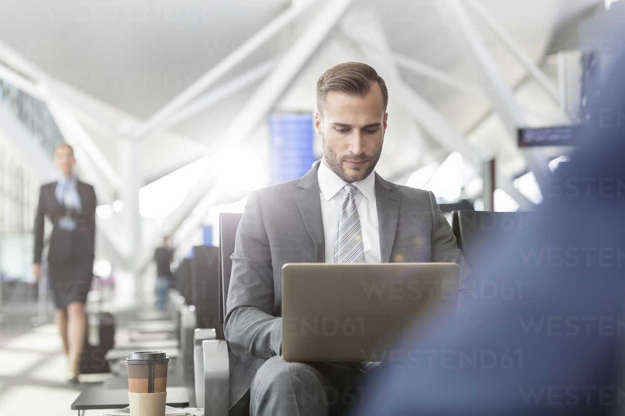 Businessman working using laptop in airport departure area - CAIF10256 - Agnieszka Olek/Westend61