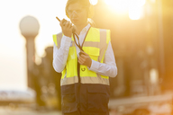 Air traffic controller using walkie-talkie on airport tarmac - CAIF10262