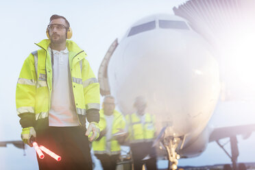 Air traffic controller standing in front of airplane on airport tarmac - CAIF10268