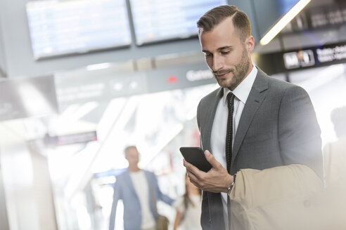 Businessman texting with cell phone in airport concourse - CAIF10271