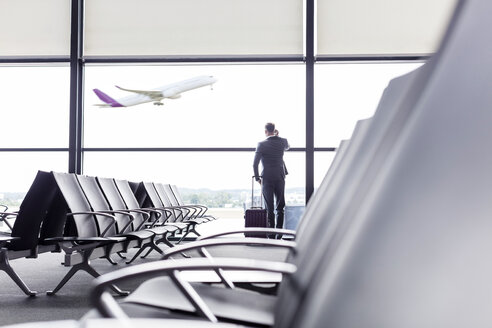 Businessman with suitcase talking on cell phone at airport departure area window - CAIF10277