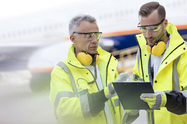 Air traffic controllers with clipboard talking on airport tarmac - CAIF10283