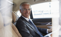 Portrait smiling businessman riding in back seat of town car - CAIF10286