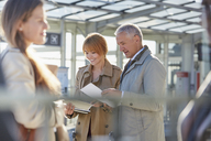 Business people reviewing paperwork in airport - CAIF10289