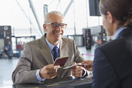 Smiling businessman giving passport to customer service representative at airport check-in counter - CAIF10298