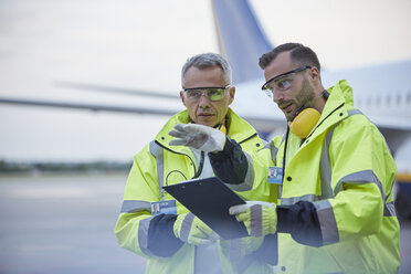 Air traffic control ground crew workers with clipboard talking on airport tarmac - CAIF10304