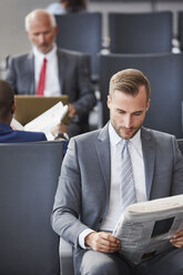 Businessman reading newspaper waiting in airport departure area - CAIF10307